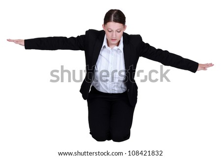 Kneeling businesswoman with arms stretched - stock photo
