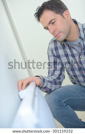 Kneeling by a radiator - stock photo