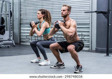 Kneeling muscular couple exercising with kettlebells - stock photo