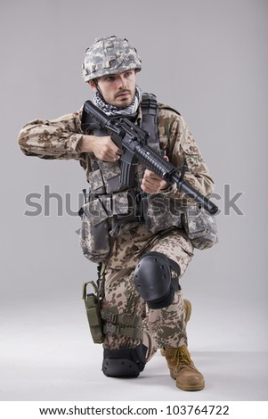 Kneeling Soldier with machine gun in studio - stock photo