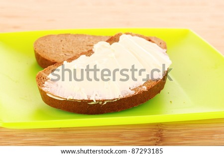 knife and a bread with butter on the plate - stock photo