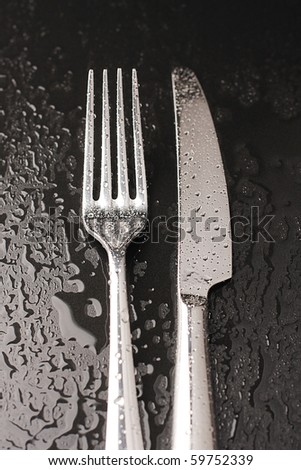 Knife and fork on a black background with water