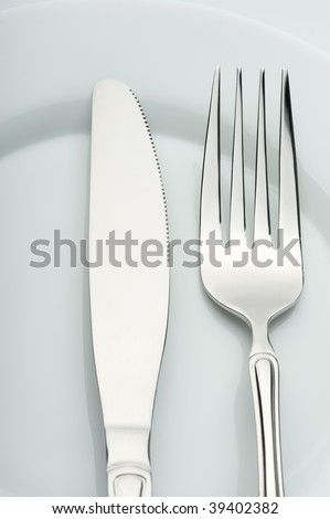 Knife and fork on a plate - stock photo