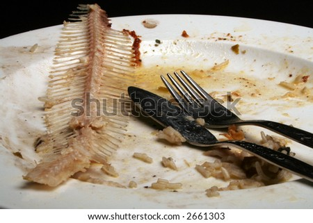 Knife and fork on dirty plate with fishbone - stock photo