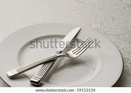 knife and fork on plate, high quality, with ornate table cloth as background