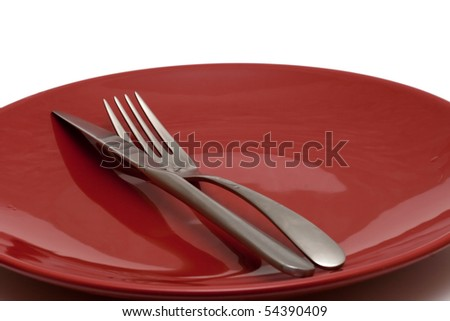 knife and fork on red shiny plate