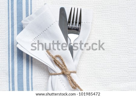 Knife and fork with blue and white linen and space for text - stock photo