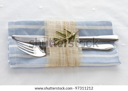 Knife and fork with napkin tied with string and natural hessian - stock photo
