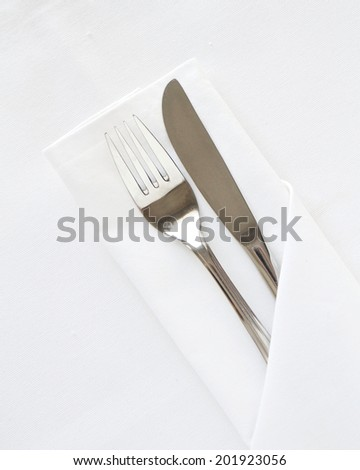 Knife and Fork with white linen and space for text - stock photo
