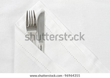 Knife and fork with white linen serviette and space for text - stock photo
