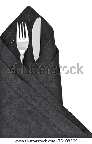 Knife and Fork wrapped in a black napkin as a table setting - stock photo