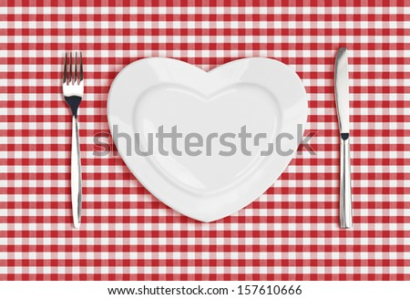 Knife, heart plate and fork on checked tablecloth - stock photo