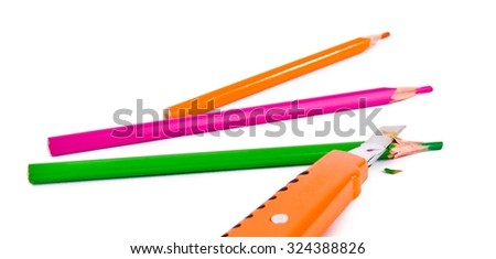Knife is sharpning the green pencil, pink and orange pencils are sitting on white backgound