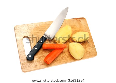 Knife, potato and carrots on a wooden board