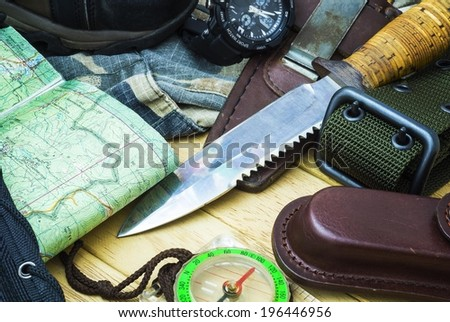 Knife surrounded by tourist equipment - stock photo