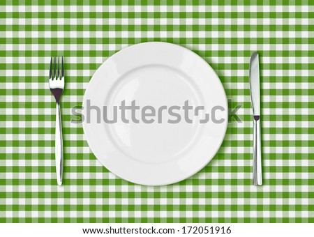 Knife, white plate and fork on green picnic tablecloth - stock photo