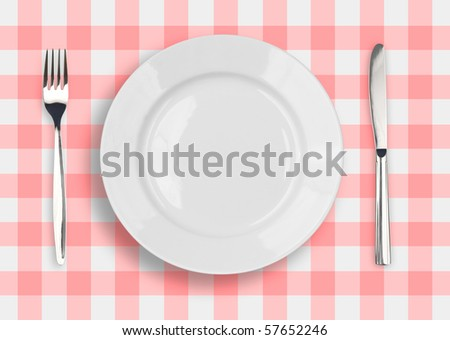 Knife, white plate and fork on red checked tablecloth - stock photo