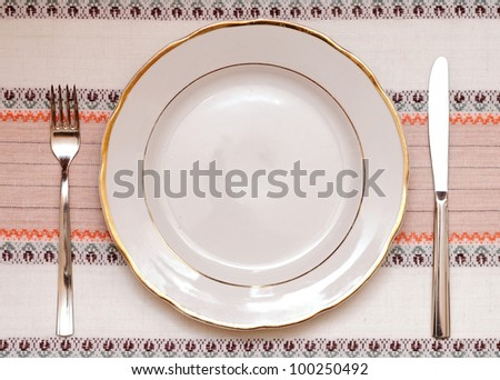 Knife, white plate and fork on tablecloth - stock photo