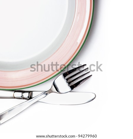 Knife, white plate and fork on white background - stock photo