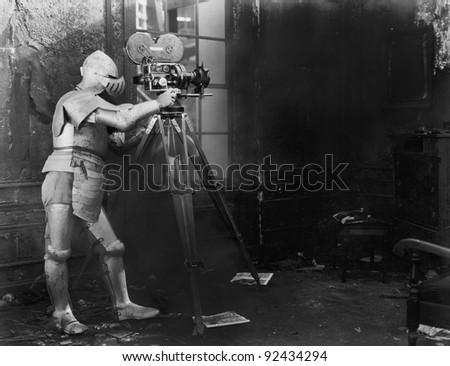 Knight at the movies, a man in an armored suit uses a film camera - stock photo