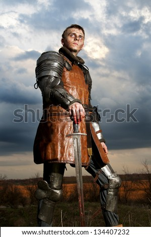 Knight holding sword on a sky background - stock photo