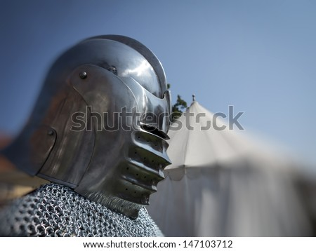 Knight in coat of mail and helmet in front of his tent ready for a fight. - stock photo