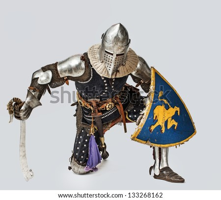 Knight lean on his knee while holding shield - stock photo