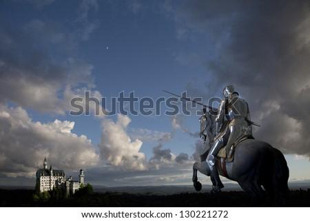 Knight on horseback, castle in background - stock photo