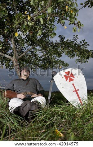 Knight resting against an apple tree