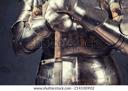 knight wearing armor and standing with two-handed sword