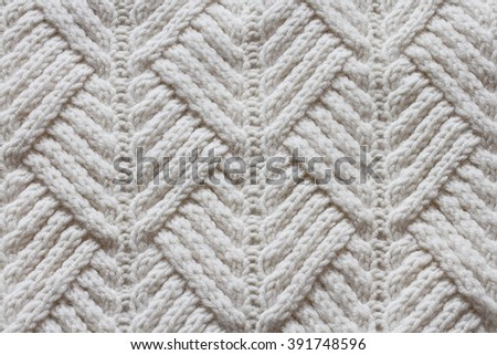 knit an interesting pattern on the canvas of white yarn  - stock photo