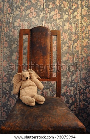 knitted bunny sitting on an old chair with background - stock photo