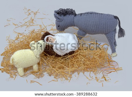 knitted donkey ,lamb and baby Jesus in manger - stock photo