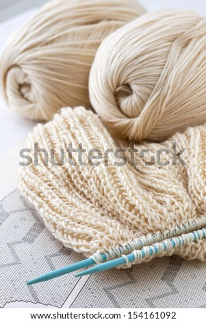 knitted fabric and knitting needles on a paper background - stock photo