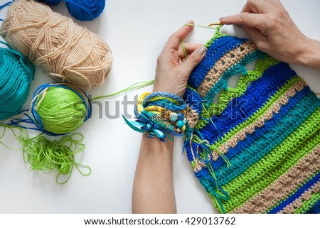 Knitted fabric of wool. Crochet. White background. View from above. Blue, green, aqua, beige color. To crochet. - stock photo