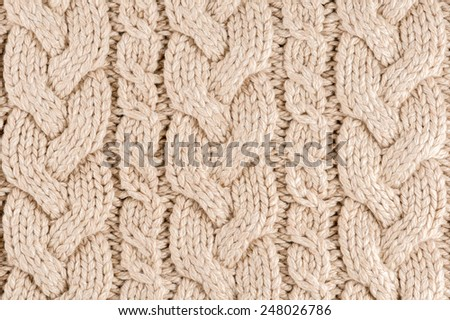 Knitted fabric texture close-up, beige color,  aran Sweater. - stock photo