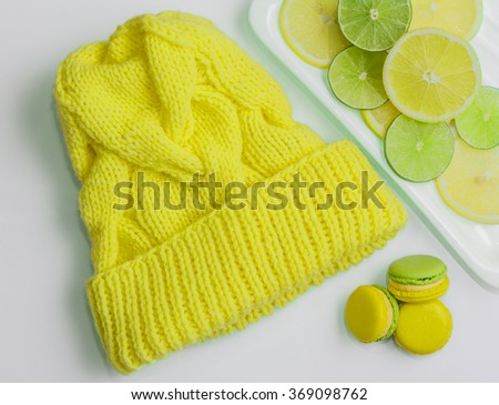 knitted hat handmade woolen threads yellow surrounded by citrus and Pancake / yellow knit cap - stock photo