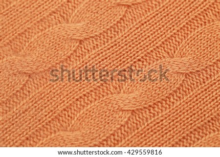 Knitted Norwegian diagonal pattern with front and reverse loop braids from orange-colored cashmere yarn, fashion background, close up - stock photo