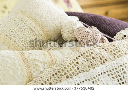 Knitted pink heart with pillows and lace composition - close up