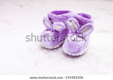 Knitted purple baby booties with rabbit muzzle over fur - stock photo