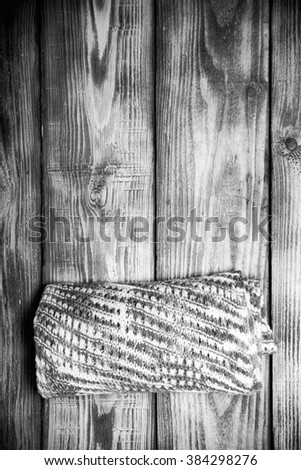 Knitted scarf on old wooden burned table or board for background. Toned.