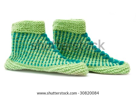 Knitted slippers on white background