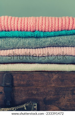 Knitted Tender  Color Sweaters, in stack on an old Trunk, vintage style, toned - stock photo