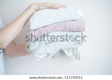 knitted things in the hands of. blonde girl with arms extended forward with knit warm clothes