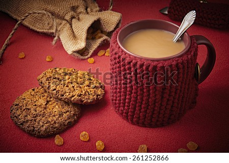 Knitted woolen mug with cookies on a table - stock photo
