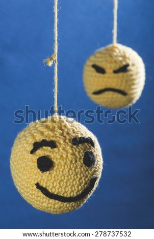 Knitted yellow emoticons on blue background - stock photo