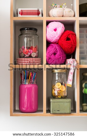 Knitting and crochet materials, jars of buttons, hooks, thread and yarn, organized in shelf with rectangular segments. - stock photo