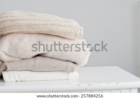 Knitting clothes in basket, on grey background - stock photo