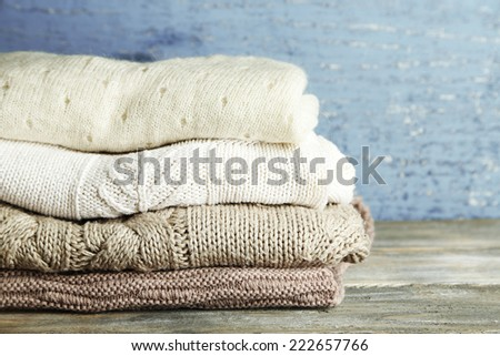 Knitting clothes on wooden background - stock photo