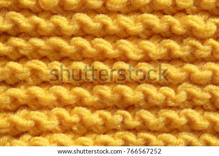 Knitting from woolen threads with a large pattern. The texture of the fibers is orange.
